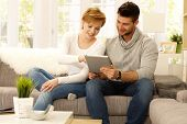 foto of sofa  - Happy young couple using tablet pc at home - JPG