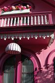 pic of martha  - bright pink gingerbread house with railing and flower box on martha - JPG