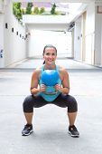 stock photo of squatting  - Woman doing the kettlebell squat for muscle strengthening exercise - JPG