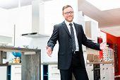 image of showrooms  - Salesman in domestic kitchen in studio or furniture showroom - JPG