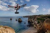 stock photo of helicopters  - A drone with raised landing gears and a camera flying in beautiful cloudy skies along spectacular sea cliffs with a calm ocean in the background - JPG