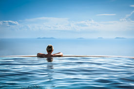 picture of adults only  - Woman relaxing in infinity swimming pool on vacation - JPG