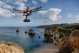 pic of cloudy  - A drone with raised landing gears and a camera flying in beautiful cloudy skies along spectacular sea cliffs with a calm ocean in the background - JPG