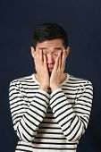 stock photo of disappointed  - Disappointed young Asian man covering his face by palms  - JPG
