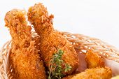 foto of crisps  - Crisp crunchy golden chicken legs and wings deep fried in bread crumbs and served with a bowl of dip in a wicker basket for a delicious appetizer