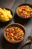 stock photo of sweet-corn  - Two rustic bowls of vegetarian chili dish made with kidney bean carrot zucchini bell pepper sweet corn tomato onion garlic with tortilla chips on the side photographed with natural light  - JPG