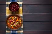 foto of kidney beans  - Overhead shot of a rustic bowl of vegetarian chili dish made with kidney bean carrot zucchini bell pepper sweet corn tomato onion garlic raw kidney beans in bowl above photographed on dark wood with natural light - JPG