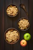 stock photo of crisps  - Overhead shot of three rustic bowls of baked apple crumble or crisp wooden spoons and fresh apples on the side photographed on dark wood with natural light - JPG