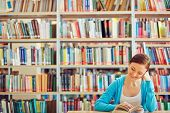 foto of student  - Curious student reading interesting book in library - JPG