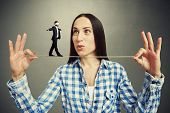 foto of blindfolded man  - amazed woman looking at small walking man on the rope - JPG