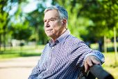 pic of bench  - Portrait of worried senior man siting on bench in park - JPG