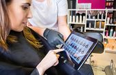 stock photo of hair dye  - Beautiful young woman with hairdresser choosing new color in hair dye palette on a digital tablet - JPG
