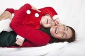 picture of santa baby  - tender and funny portrait of one year age caucasian blonde cute lovely baby Santa Claus Christmas disguise with brunette woman mother red cardigan green sweater embraced laughing together lying on white floor background - JPG