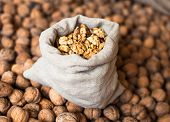 foto of walnut  - Walnuts kernels in the small linen sack on the pile of walnuts in shell - JPG