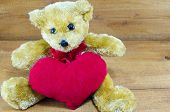 picture of teddy  - Brown teddy bear hugging a big red heart on a wooden table - JPG