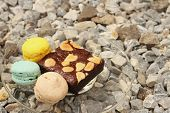 stock photo of brownie  - Brownies with Macaron in a dish on the background of rocks - JPG