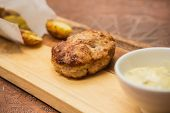 picture of beef-burger  - Succulent cooked beef burger with potato on a wood plate - JPG