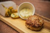 foto of beef-burger  - Succulent cooked beef burger with potato on a wood plate. ** Note: Shallow depth of field - JPG