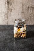 stock photo of muse  - A jar of healthy swiss museli yogurg blackberries and honey on a black slate background - JPG