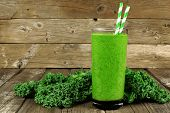 foto of kale  - Healthy green smoothie with kale in a glass against a rustic wood background - JPG