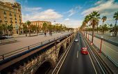 stock photo of tree lined street  - Cars and people on late afternoon streets and pedestrian ways in Seaside Barcelona - JPG