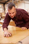 foto of carpentry  - Carpenter Finishing Wood In Carpentry Workshop - JPG