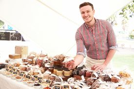 stock photo of stall  - Stall Holder At Farmers Food Market Selling Nuts And Seeds - JPG