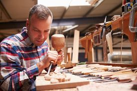 picture of chisel  - Carpenter Carving Wood Using Chisel - JPG