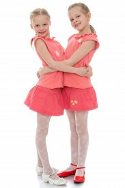 stock photo of identical twin girls  - Two charming little girls sisters hug each other - JPG