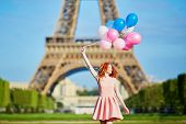Woman In Pink Dress With Bunch Of Balloons Dancing Near The Eiffel Tower In Paris, France poster