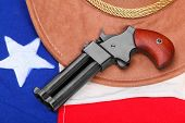 foto of derringer pistol  - Double derringer pistol on a american flag - JPG