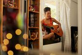 Black Woman Singing And Playing Guitar At Home poster