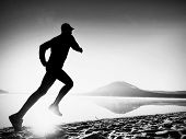 Man Exercising On Beach.  Silhouette Of Active Man Exercising  And Stretching At Lake poster