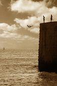 Постер, плакат: Подростки прыжки от стены древней крепости в Средиземное море в Акко Израиль сепия t