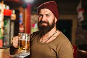 Handsome Bearded Hipster Holds Glass Of Beer. Beer Pub. Stylish Guy At Cafe Pub. Beer Time. Cheerful poster