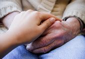 Young Caregiver Holding Senior's Hands