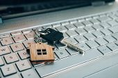 Metallic Key On Key Ring With House Symbol Lying On Laptop Keyboard. Real Estate And Internet Concep poster