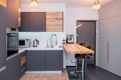 Modern Kitchen Interior With Lights On. Brown Wooden Table And Bar Stools, Coffee Machine. Contempor poster