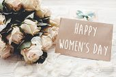 Happy Womens Day Text Sign On Craft Greeting Card And White Roses Bouquet, Gift Box On Wooden Backg poster