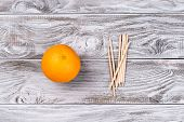 Fruit Orange And Orange Wood Sticks Cuticle Pushers For Manicure. Copyspace For Your Text, Banner. poster