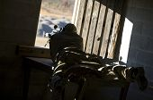 stock photo of prone  - Precision shooter prone in the dark scanning out a window - JPG