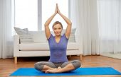 mindfulness, spirituality and healthy lifestyle concept - woman meditating in lotus pose at home poster