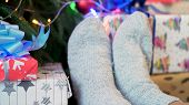 Feet In Knitted Socks Near New Year Presents On Christmas Tree Background, Winter Holidays And Home  poster