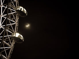 picture of ferris-wheel  - Black and white close up of illuminated ferry wheel with moon over it on a black sky - JPG