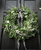 foto of christmas wreath  - Eucalyptus Christmas wreath hung on a black door - JPG
