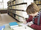 picture of shelving unit  - Young male student doing homework on table in the library - JPG