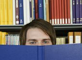 stock photo of shelving unit  - Closeup portrait of a young man peeking over opened book in library - JPG