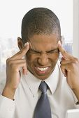 Mixed race businessman with headache