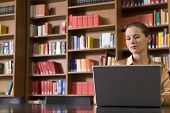 foto of shelving unit  - Beautiful and serious young woman using laptop in the library - JPG
