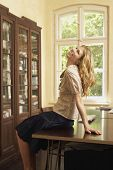 stock photo of shelving unit  - Side view of a cheerful young woman sitting on table in living room with head thrown back - JPG